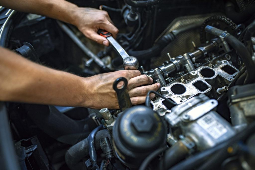Car mechanic at a garage fixing an engine.