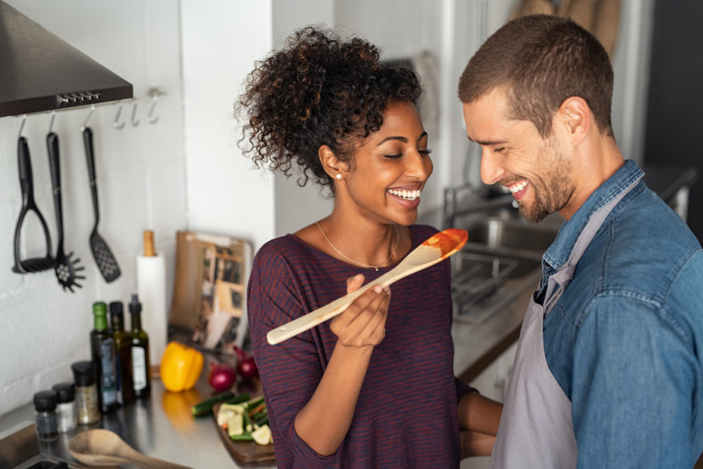 Young couple tasting tomato sauce while cooking in the kitchen.