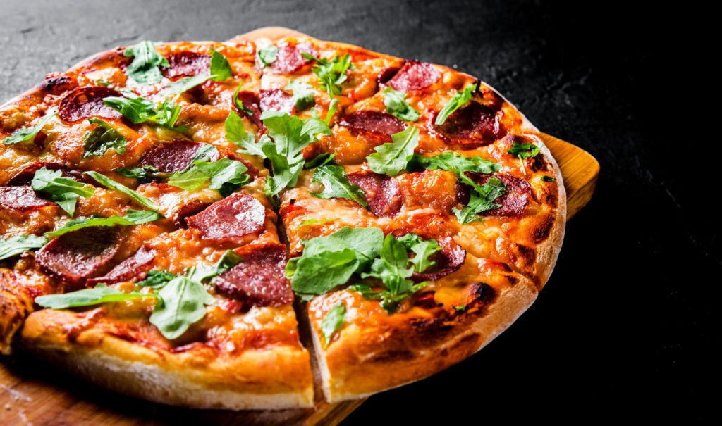 a pizza with leafy greens and pepperoni