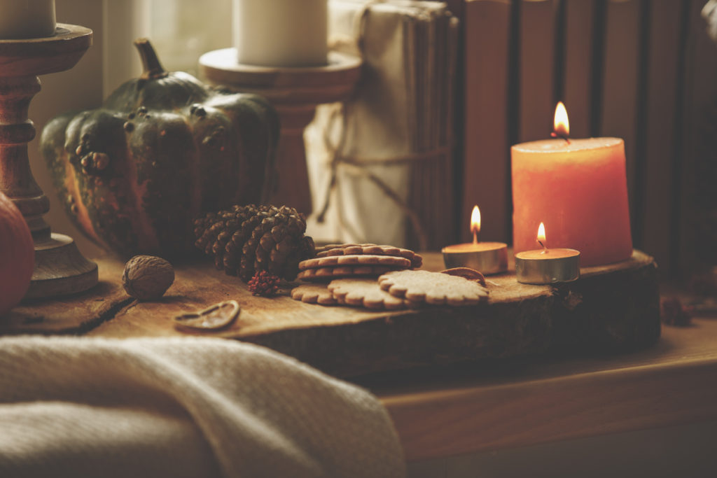 Close-up of still life composition of lit candles, cookies and pumpkin set up on a wooden table