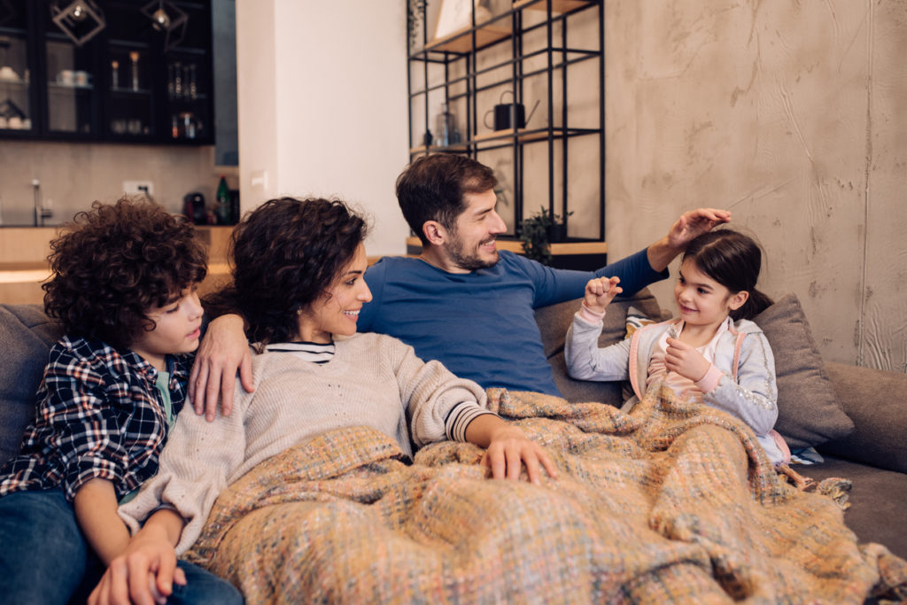 Young couple and their two children relaxing on the couch.