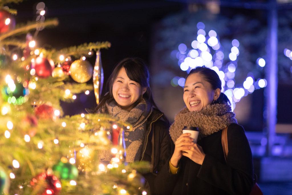 Happy female friends enjoying Christmas lights