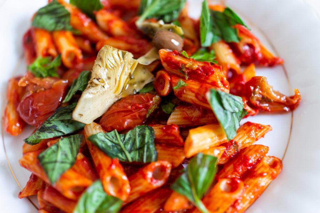 Fresh vibrant red tomato sauce on penne pasta.