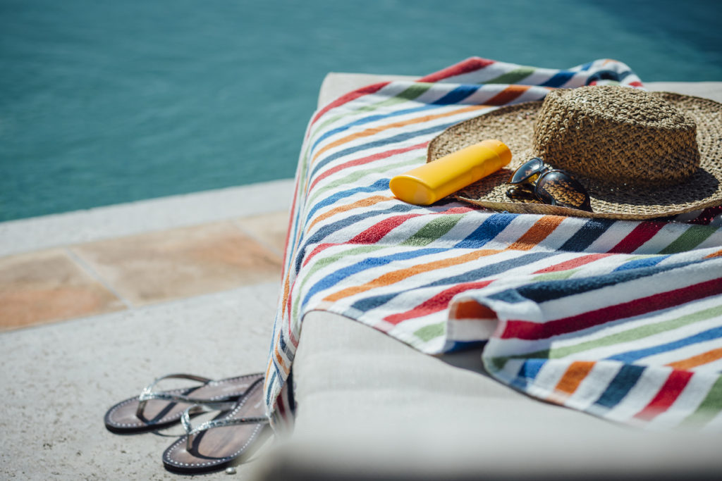 Woman's hat and towel sitting by the pool
