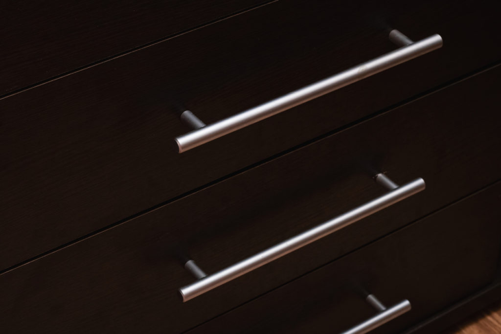Wooden drawer shelves with metal handles closeup