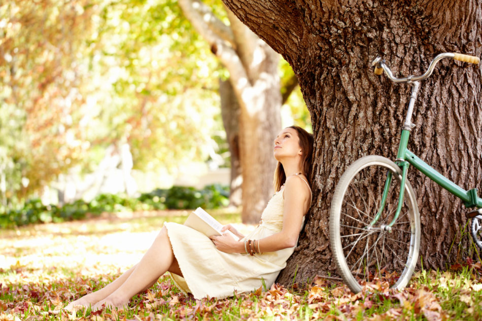 woman sitting in shade under tree