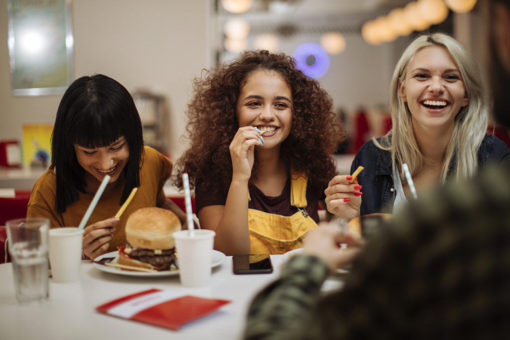 female friends laughing while eating burgers and fries in a restaurant